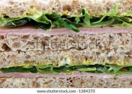 Healthy wholemeal brown rye bread sandwich, with egg, ham, mustard, and mayonnaise, copyspace, on white, macro, close up.