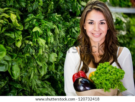 Healthy woman buying fresh vegetables at the supermarket
