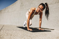 Healthy woman doing mountain climbers exercise. Female in sportswear exercising on a mat outdoors.