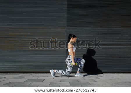 Healthy woman doing strength training with dumbbells against black line background outdoors, athletic female lifting weights while working out against wall with copy space for your text message