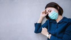 Healthy woman in green medical protective mask showing gesture stop. Health protection and prevention during flu and infectious outbreak or Covid-19 at congrete wall