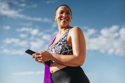 Healthy woman in sportswear with mobile phone after workout session. Curvy woman taking a break from workout looking away and smiling outdoors.