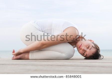 Healthy woman resting and curl up in fetal position outdoor at sea: yoga pose.