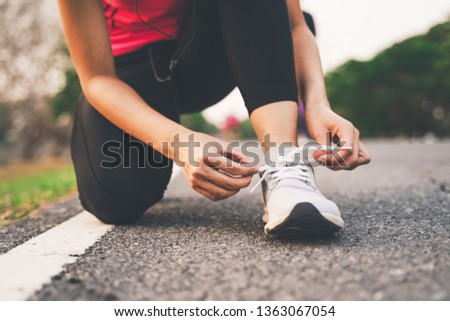 Healthy woman runner legs running exercise jogging on road, Woman fitness jog workout in the park during sunset #1363067054