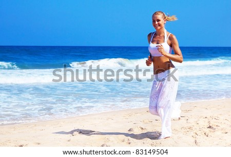 Healthy woman running on the beach, doing sport outdoor, freedom, vacation, heath care concept with copy space over natural background