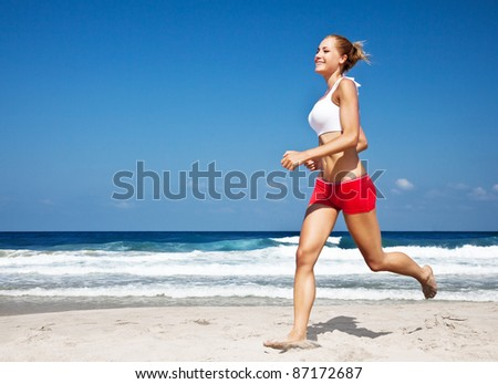 Healthy woman running on the beach, doing sport outdoor, freedom, vacation, heath care concept with copy space over natural blue background