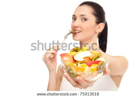 healthy woman showing healthy food, bowl with fruit salad in focus, isolated