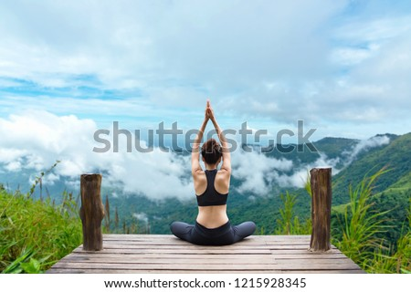 Healthy woman yoga lifestyle balanced practicing meditate and zen energy exercise sport yoga outdoors on the bridge in morning the mountain nature. Healthy life Concept.