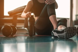 Healthy women are sitting and relaxing after exercising with whey protein after workouts at the indoor gym.