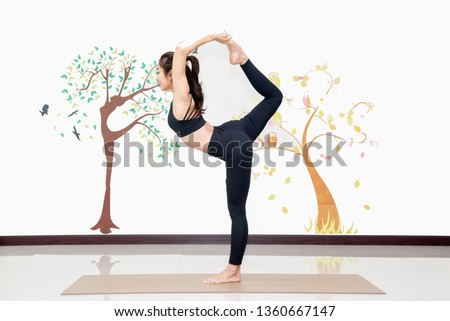 healthy women practicing yoga in gym . standing stretching in Tree pose,Dance Pose,Dancing Pose,Natarajasana both hands grabbing onto the back foot with overhead grin, foot away from the head #1360667147