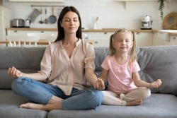 Healthy young adult parent mother and little child daughter doing yoga exercise sit on sofa at home, calm mom teaching cute small kid girl learning practice family meditation relax together concept