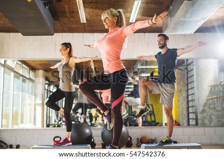 Healthy young athletes doing exercises at gym.