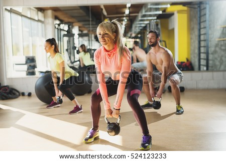 Shutterstock Healthy young athletes doing exercises with kettlebells, at fitness studio.