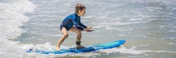 Healthy young boy learning to surf in the sea or ocean BANNER, LONG FORMAT