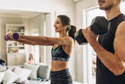 Healthy young couple doing exercises with dumbbells at home. Fit young woman with man doing weights workout indoors in living room.