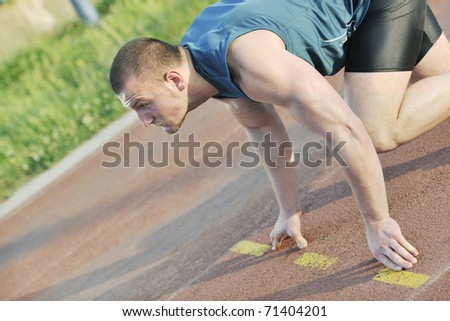 healthy young man at start line ready for run race and win