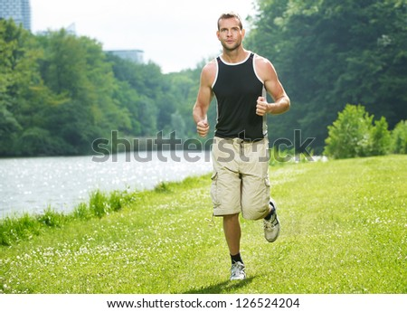 Healthy young man running outdoors in the park - stock photo