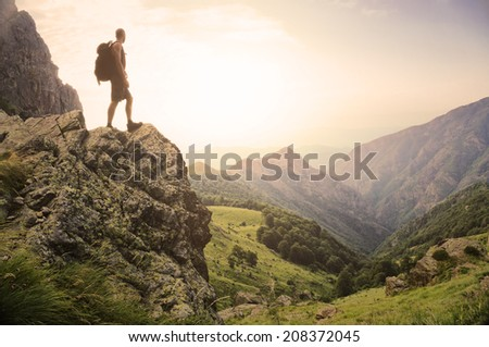 Healthy young man standing on top of a rock high in the mountains enjoying the natural beauty in the morning light
