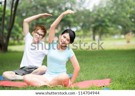 Healthy young people doing stretching exercises simultaneously