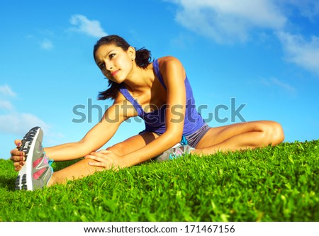 healthy young pretty mixed race woman stretching her leg during exercise in grass right before a work out Horizontal shot