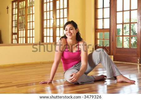 Healthy young smiling woman with dark hair sitting on the wooden floor in her exercise studio. Resting after yoga stretches associated with health and wellness, as well as general fitness and dieting.