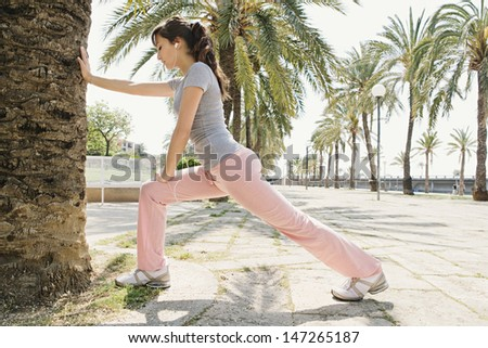 Healthy young woman exercising and stretching leaning on a trunk in a palm tree avenue and listening to music with her head phones during a sunny day.