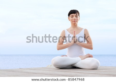 Healthy young woman meditating in yoga lotus pose at sea