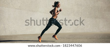 Healthy young woman running in morning. Fitness model exercising in morning outdoors. Panoramic side shot of fit woman.
