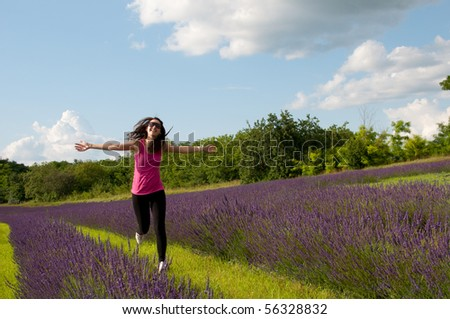 Healthy young woman runs with arms outstretched on lavender field