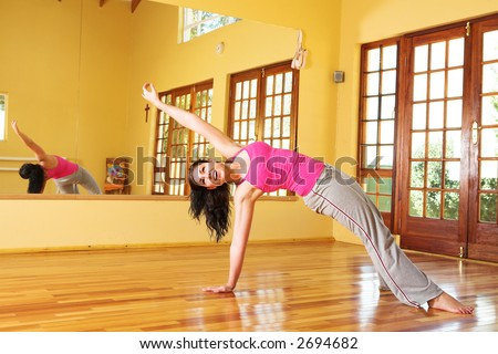 Healthy young woman with dark hair exercising in studio. Yoga stretches associated with health and wellness, as well as general fitness and dieting.