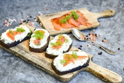 Healty salmon sandwiches with  flaxseed bread, spiced cottage cheese on  industrial background. Party food .Light office lunch