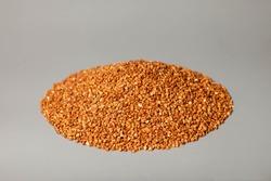 Heap bunch of buckwheat close up on gray background. Macro photo food buckwheat groats. Texture background grain buckwheats groats. Image food product for porridge cooking. Copy space