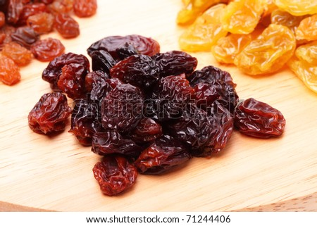 Heap large raisins on a cutting board