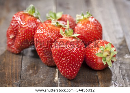 Heap of a lot of fresh red strawberries on wooden table top