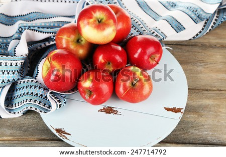Heap of apples on board with dish cloth on wooden table background