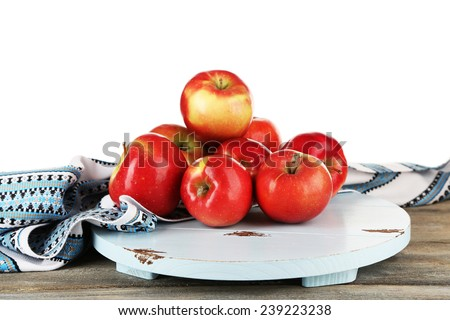 Heap of apples on board with dish cloth on wooden table isolated on white background