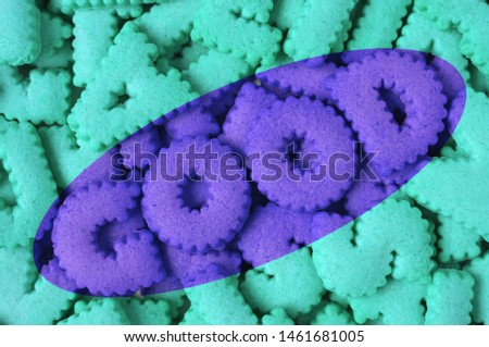 Heap of aqua blue alphabet shaped cookies of the word GOOD in purple colored #1461681005