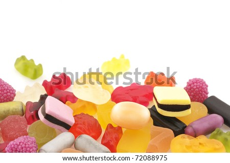 Heap of assorted colorful candy on white background.