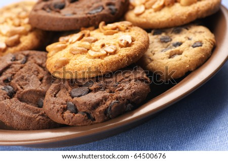 Heap of assorted cookies in brown ceramic plate on blue cloth.