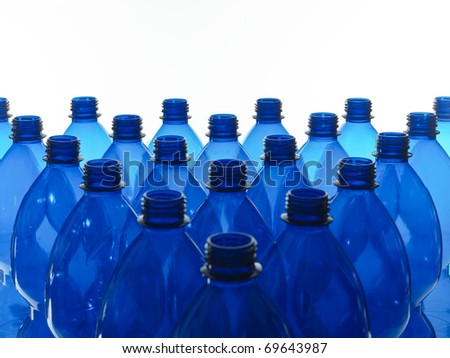 heap of blue plastic bottles on a white background