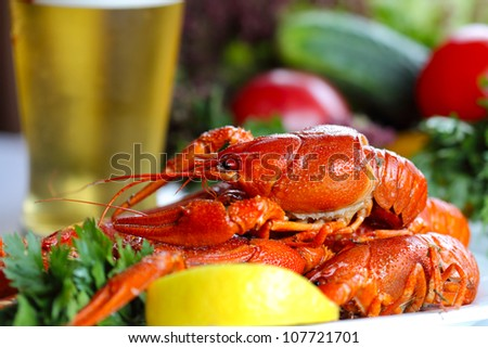 Heap of boiled crayfish, glass of beer and garnish (closeup, selective focus)