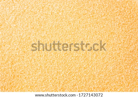 Heap of cane sugar. Top view. Background of brown sugar. Dark sugar background. Sugar for cooking. Selective focus.