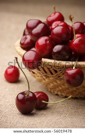 Heap of cherries in wicker basket on brown linen canvas.