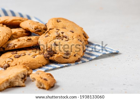 Heap of chocolate chip cookies on a gray table close-up. Sweet breakfast. Stack of traditional chip cookies with chocolate chunks.