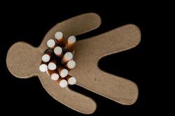 Heap of cigarettes inside a cardboard man on a dark background. Addiction to cigarettes. Smoking kills