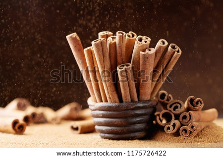 Heap of cinnamon sticks and ground cinnamon with dust effect. Aromatic spice. #1175726422