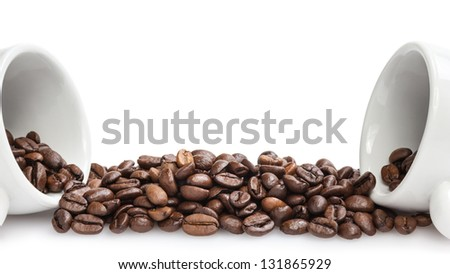 heap of coffee beans with two cups, isolated on white