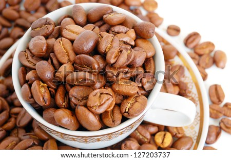 heap of coffee beans within cap on saucer