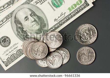 heap of coins and a hundred dollar bills on a gray - stock photo