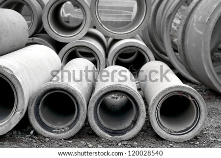 Heap of concrete pipes on construction site
